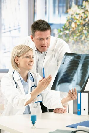 medical physician: Medical team discussing diagnosis of x-ray image in office.