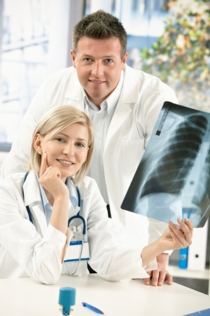 Portrait of medical doctors smiling at camera holding x-ray image. photo