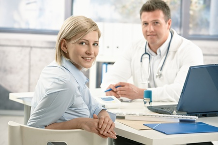 woman doctor: Smiling woman sitting in doctors office on appointment, looking at camera, doctor in background.