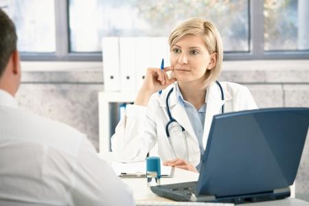 Médico escuchando paciente con concentración, sentado en el escritorio en la Oficina. Foto de archivo