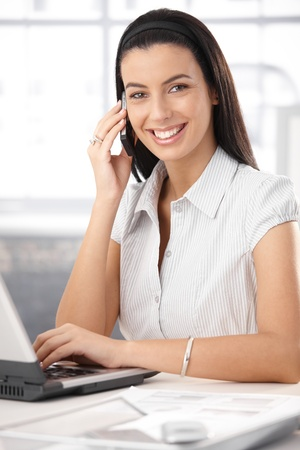Cheerful office assistant using laptop computer on mobile phone call, laughing happily at camera.