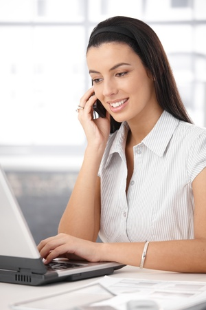 Office girl busy working on laptop computer, typing, speaking on mobile phone, smiling. Stock Photo - 8782906