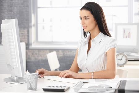 Pretty office worker girl sitting at desk in office, using desktop computer.