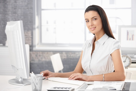 Portrait of smiling office girl sitting at desk, working on desktop computer. Stock Photo - 8782770