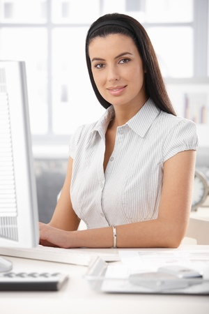 Office portrait of attractive woman sitting at desk, smiling at camera.