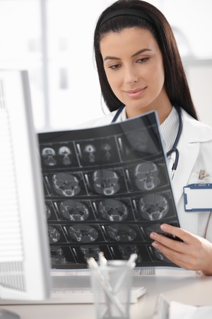 Young doctor looking at X-ray scan in office, smiling. Stock Photo - 8782834