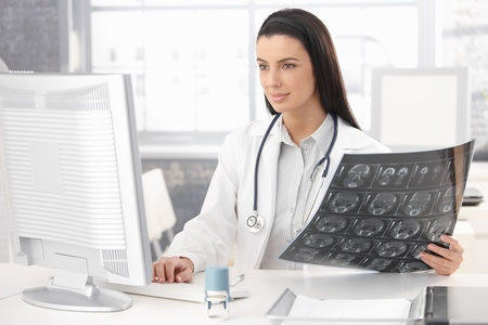 Smiling doctor sitting in office working at desk with computer and xray image.