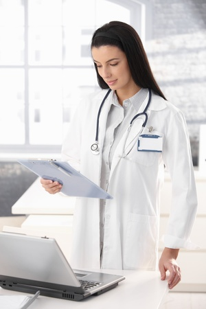 handheld: Attractive young doctor standing in office, examining clipboard handheld, smiling.