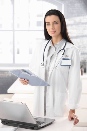 Pretty doctor standing at office desk holding clipboard. Stock Photo - 8782705