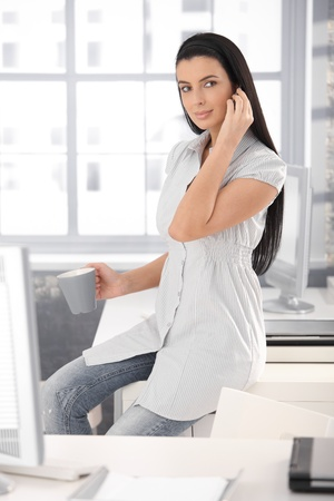 Attractive office girl on coffee break making mobile phone call, smiling. photo