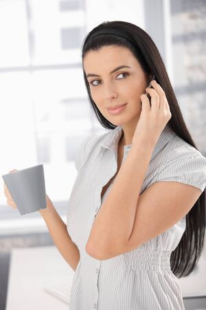 Girl in office with coffee mug, using cellphone, smiling.