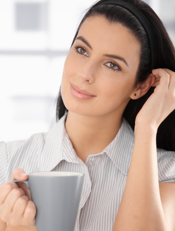 Daydreaming beauty posing with coffee mug in hand, smiling. photo