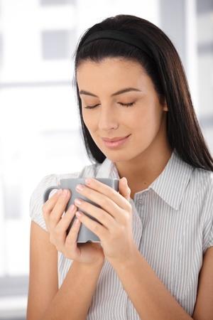 Attractive woman enjoying coffee, mug handheld, eyes closed, smiling. photo