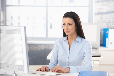 Attractive girl working on desktop computer in office, looking at screen, smiling. photo