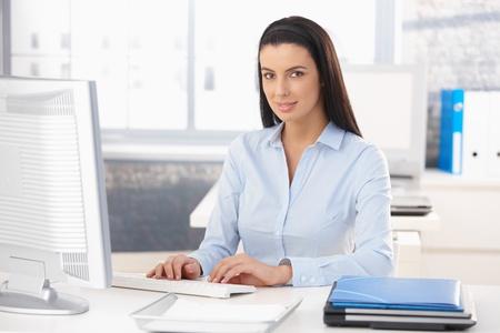 secretaria: Retrato de oficina feliz trabajador sentado en el escritorio, trabajando con el ordenador de sobremesa, sonriendo a la c�mara.