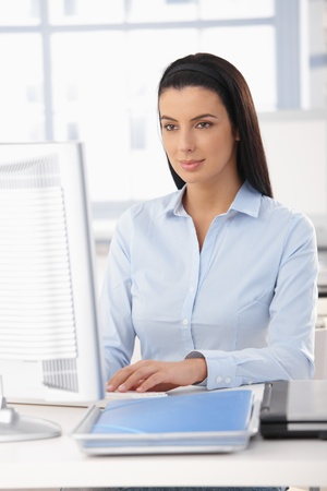 desktop computers: Pretty office worker girl sitting at desk, looking at computer screen, smiling.