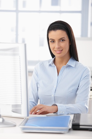 executive assistants: Portrait of happy office girl working at desk with computer, smiling at camera.