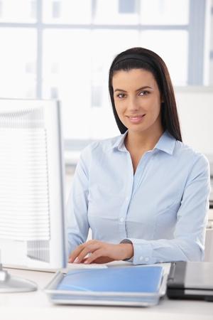 secretarias: Retrato de ni�a feliz de oficina trabajando en escritorio con equipo, sonriendo a la c�mara. Foto de archivo