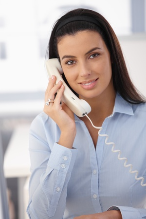 black secretary: Portrait of office girl on landline call, smiling at camera. Stock Photo