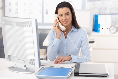 secretary office: Portrait of smiling woman working in office, using computer and landline phone. Stock Photo