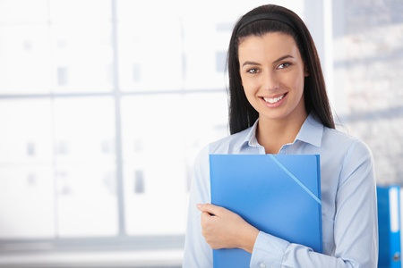 Portrait of happy woman in office, standing with folder, smiling at camera. photo