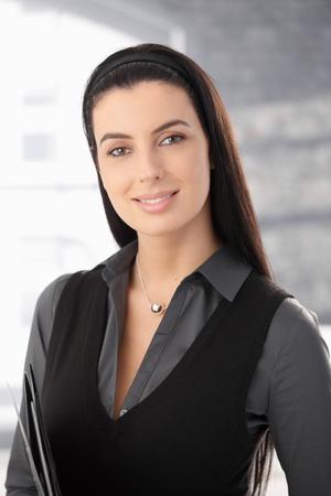 Ritratto di donna intelligente di capelli scuri lunghi sorridere alla telecamera.