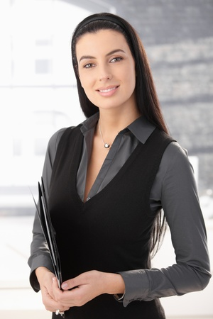 Portrait of smart office worker woman standing in office with document folder, smiling.