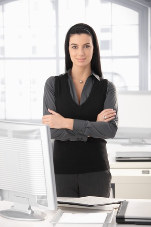 Portrait of smart office girl standing at desk with arms folded, smiling. Stock Photo - 8782937