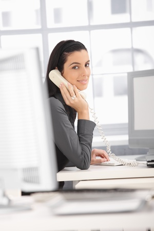 Smiling office worker woman sitting at desk on landline phone call, looking at camera. photo