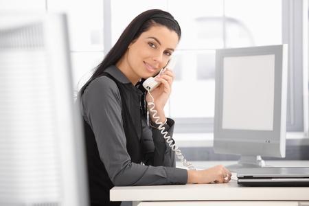 Pretty office girl at work, using landline phone, smiling at camera. photo