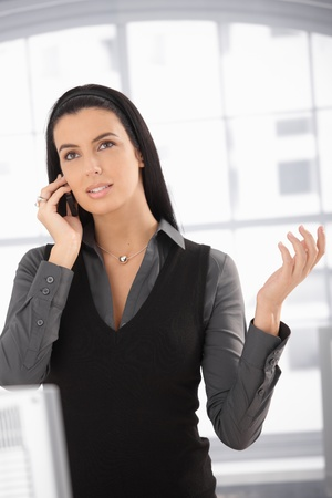 Attractive woman speaking on mobile phone, looking up, gesturing, photo