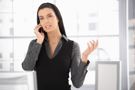 Pretty woman standing in office, speaking on mobile phone, gesturing, concentrating.