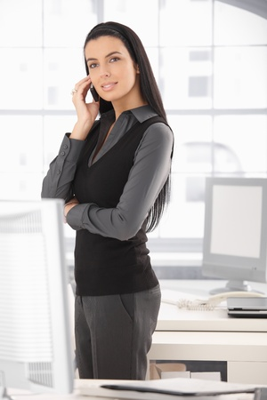 Elegant businesswoman standing at office desk, speaking on mobile phone. Stock Photo - 8782830