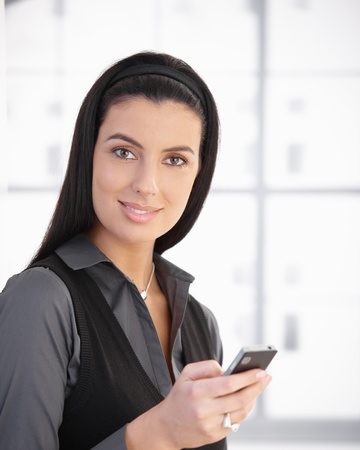 Portrait of beautiful woman using cellphone, smiling at camera. photo