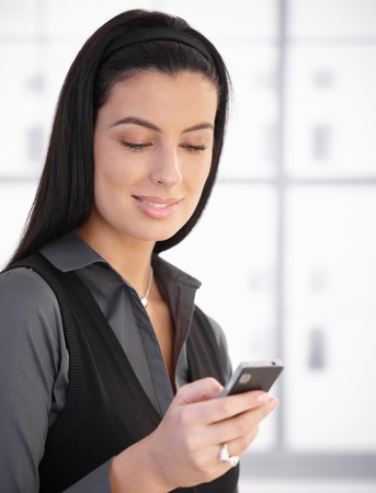 sms text: Portrait of smiling woman using cellphone, texting,