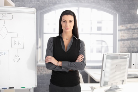 Pretty businesswoman standing at whiteboard in office with arms folded, smiling.