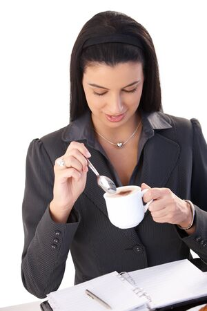 Businesswoman enjoying cappuccino while at work using personal organizer, high angle view. photo