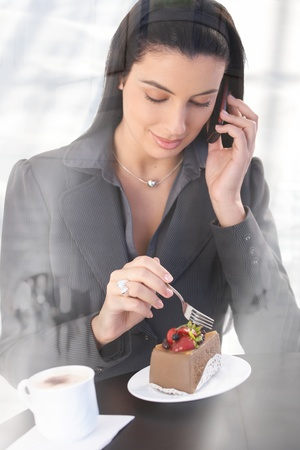 Smart office worker woman on phone call, sitting in cafe, having chocolate cake and coffee, smiling, picture through window. photo