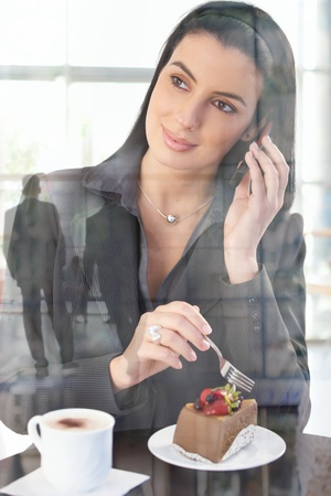 Businesswoman in office cafe enjoying cake and coffee, on mobile phone call, smiling, picture through window, office lobby reflecting. photo