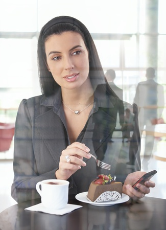 breaking through: Businesswoman in office cafe having cake and cappuccino, holding cellphone, looking through window, lobby reflection.