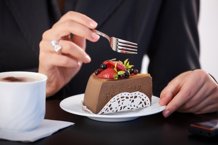 dessert fork: Portrait of tasty cake and coffee, female hand holding fork.