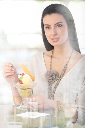Happy woman having ice cream cup at cafe table, smiling, picture through window. photo