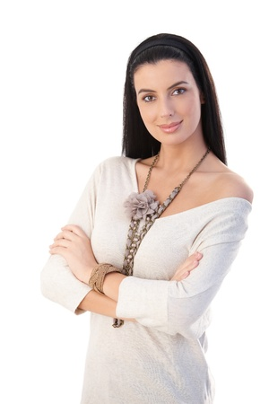 Portrait of pretty trendy woman wearing fashion accessories standing with arms folded, smiling at camera,