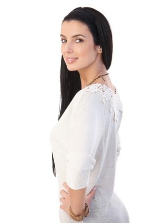 Beautiful woman with long dark hair posing in studio, smiling happily at camera. photo