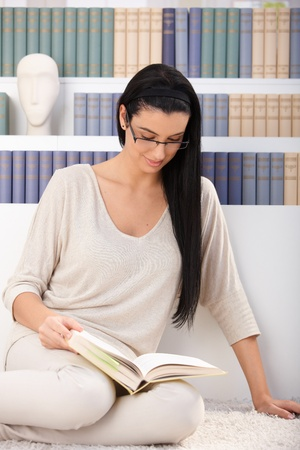 Pretty woman sitting on floor reading book at home. photo