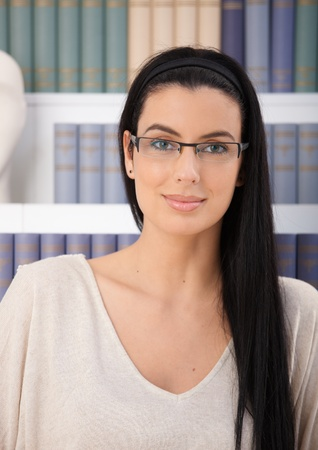 book shelf: Portrait of smiling woman in glasses looking at camera in front of book shelf.