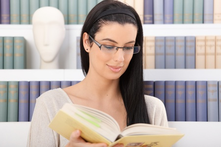 Smiling woman wearing glasses reading book in front of book shelf. Stock Photo - 8783202