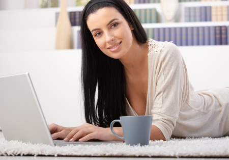 Attractive woman lying on carpet using laptop computer at home, having coffee, smiling at camera, photo