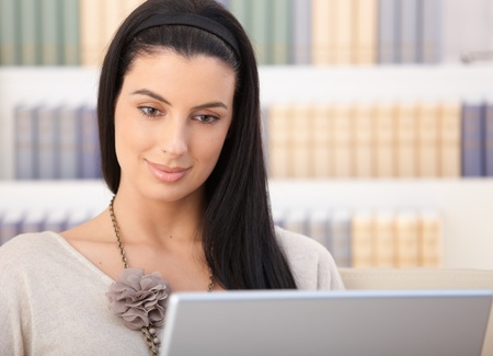 Closeup portrait of smiling woman looking at laptop computer screen at home. photo