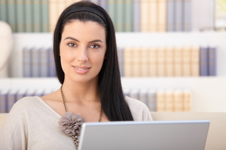 Closeup portrait of smiling woman with laptop computer at home, looking at camera. photo